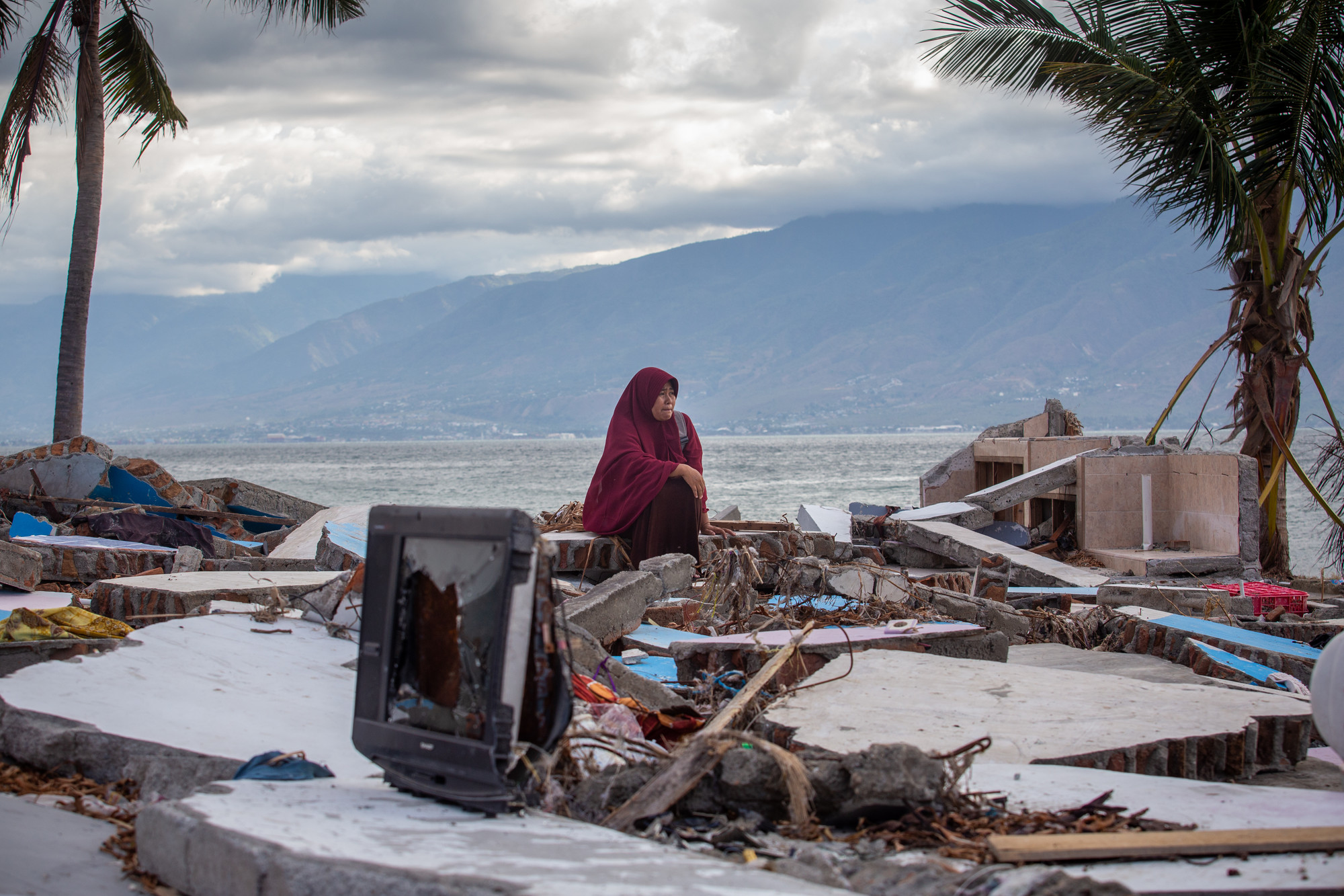 Woman sitting on pile of rubble on the beach of Sulawesi, Indonesia.