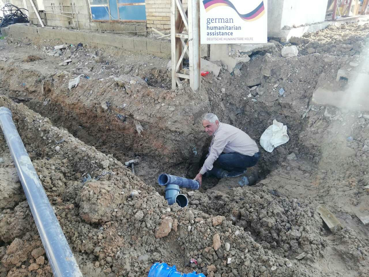 Man in a trench inserts pipes