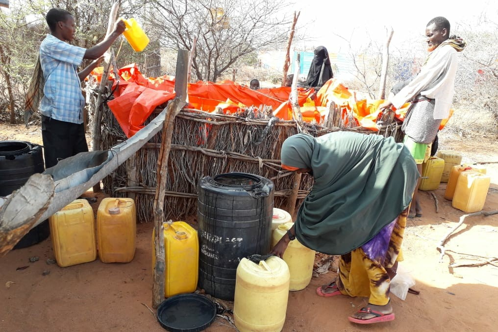 A woman in the foreground bends down to close a water canister, in the background further canisters, two men and a water reservoir.
