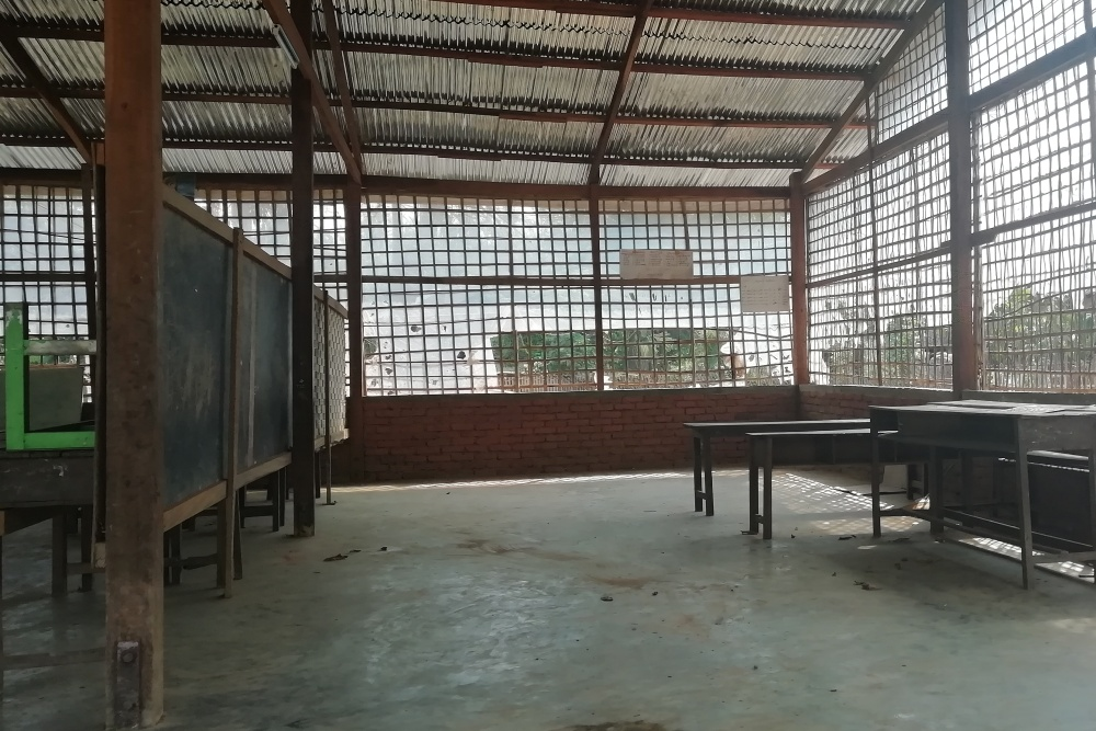 A large room with almost open exterior walls, which are only covered with a kind of net. A room divider made of blackboards, with occasional tables and chairs.