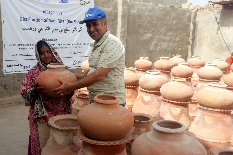 Man reaching clay pot to woman, in the background more pots