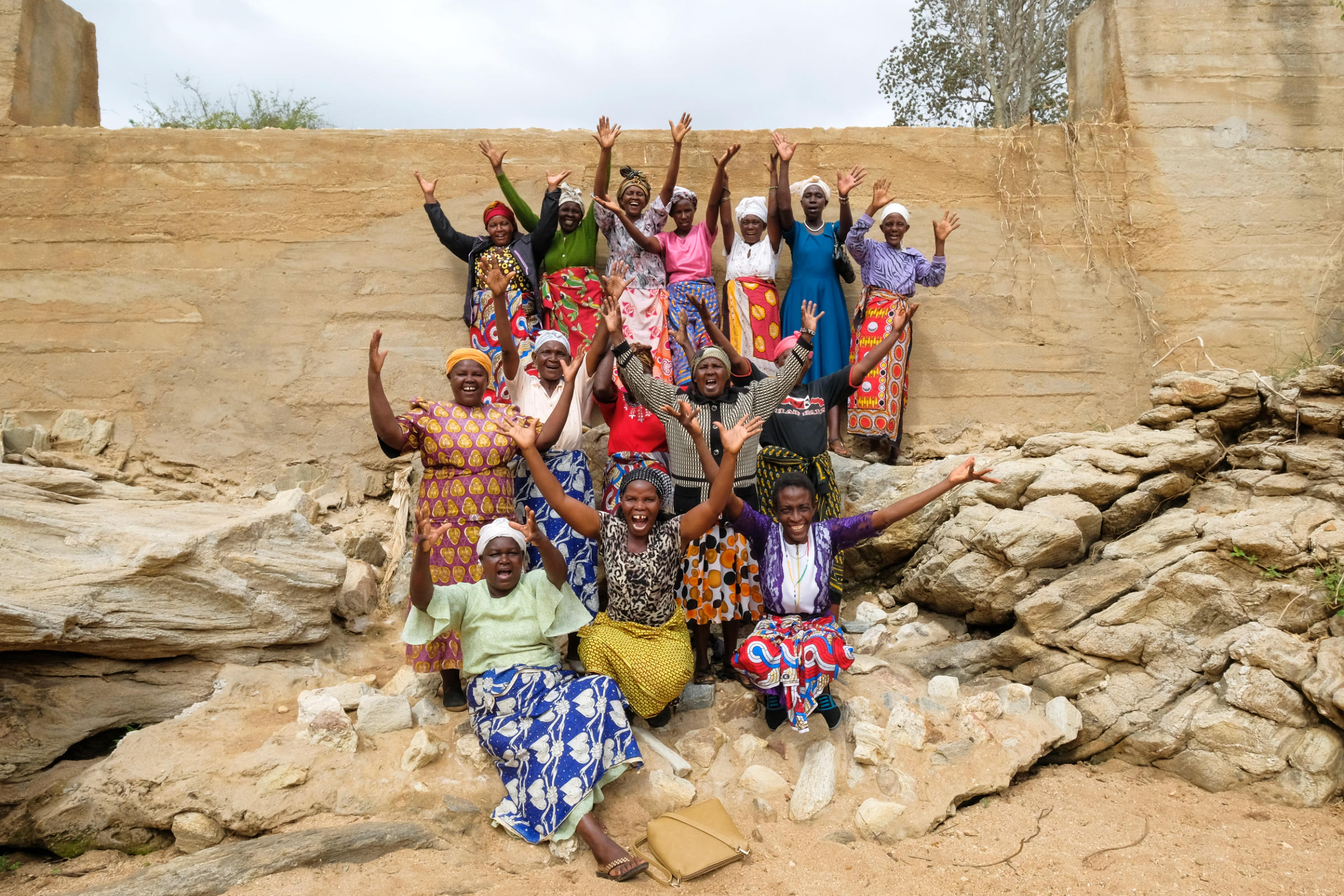 A group of women with raised hands infront of a wall