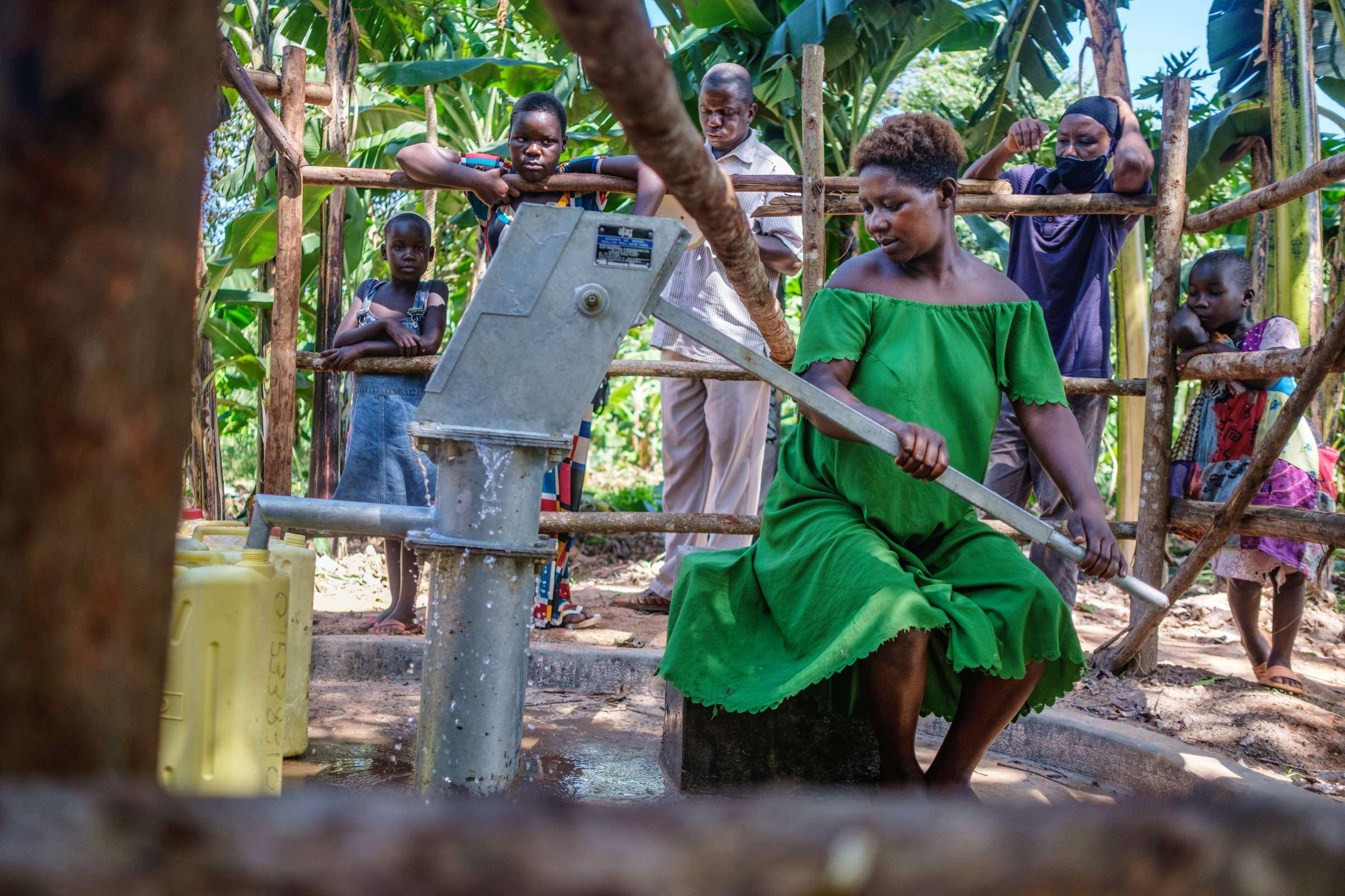 Woman sitting at hand pump and filling water canisters