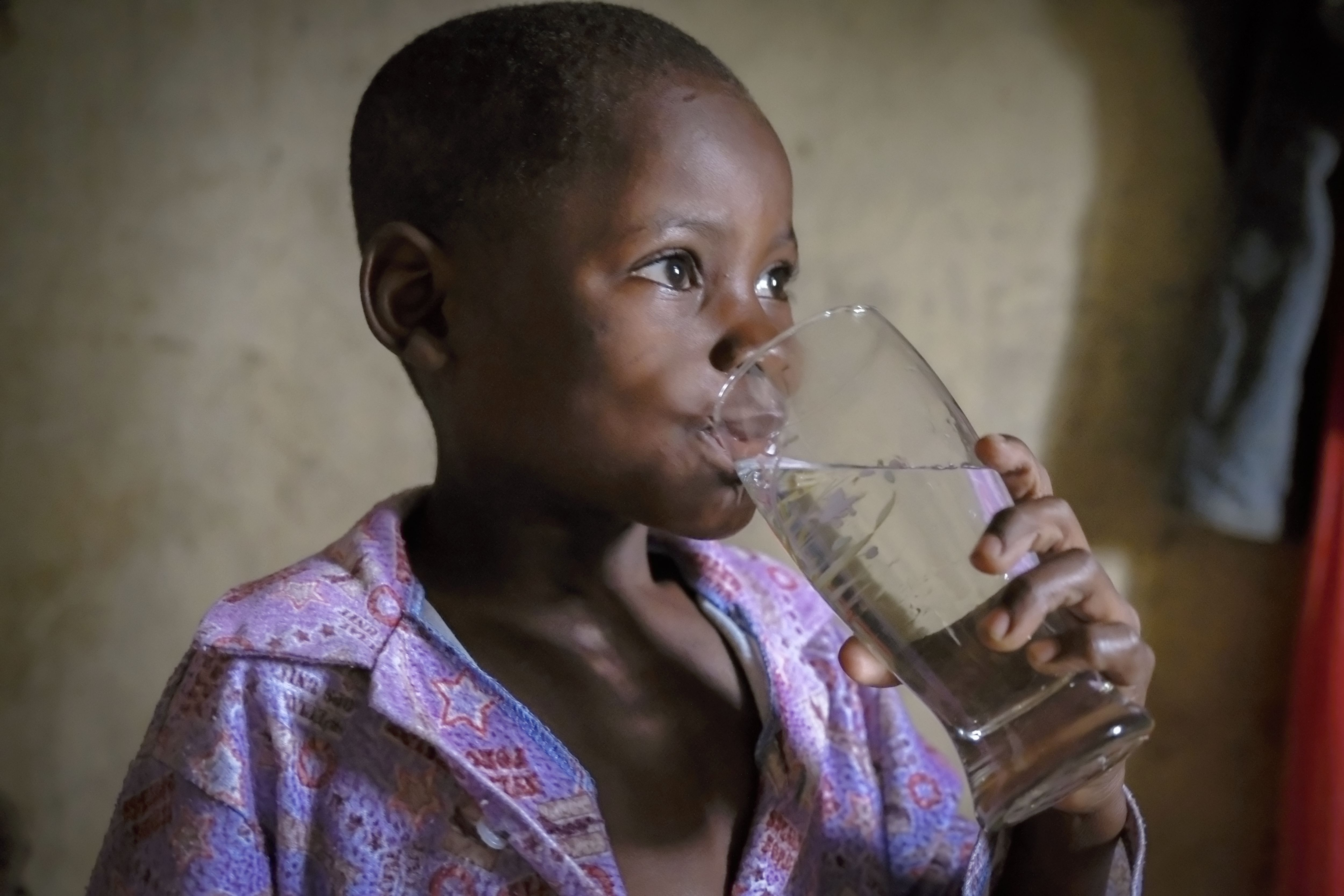 Evans Kawumbu drinking a glass of water