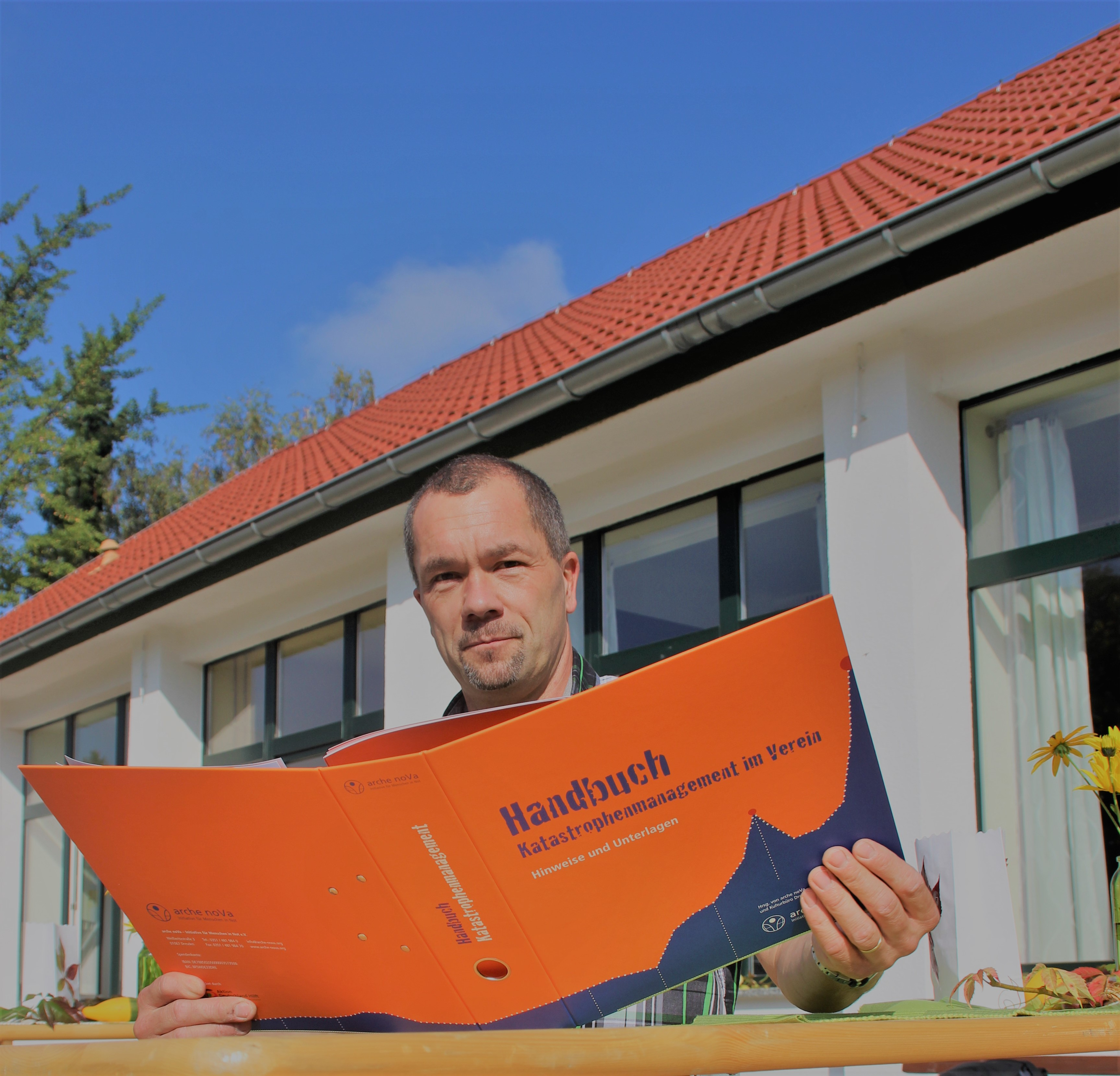 "Christoph Währer holding an orange file with the title ""Handbuch Katastrophenmanagement"""