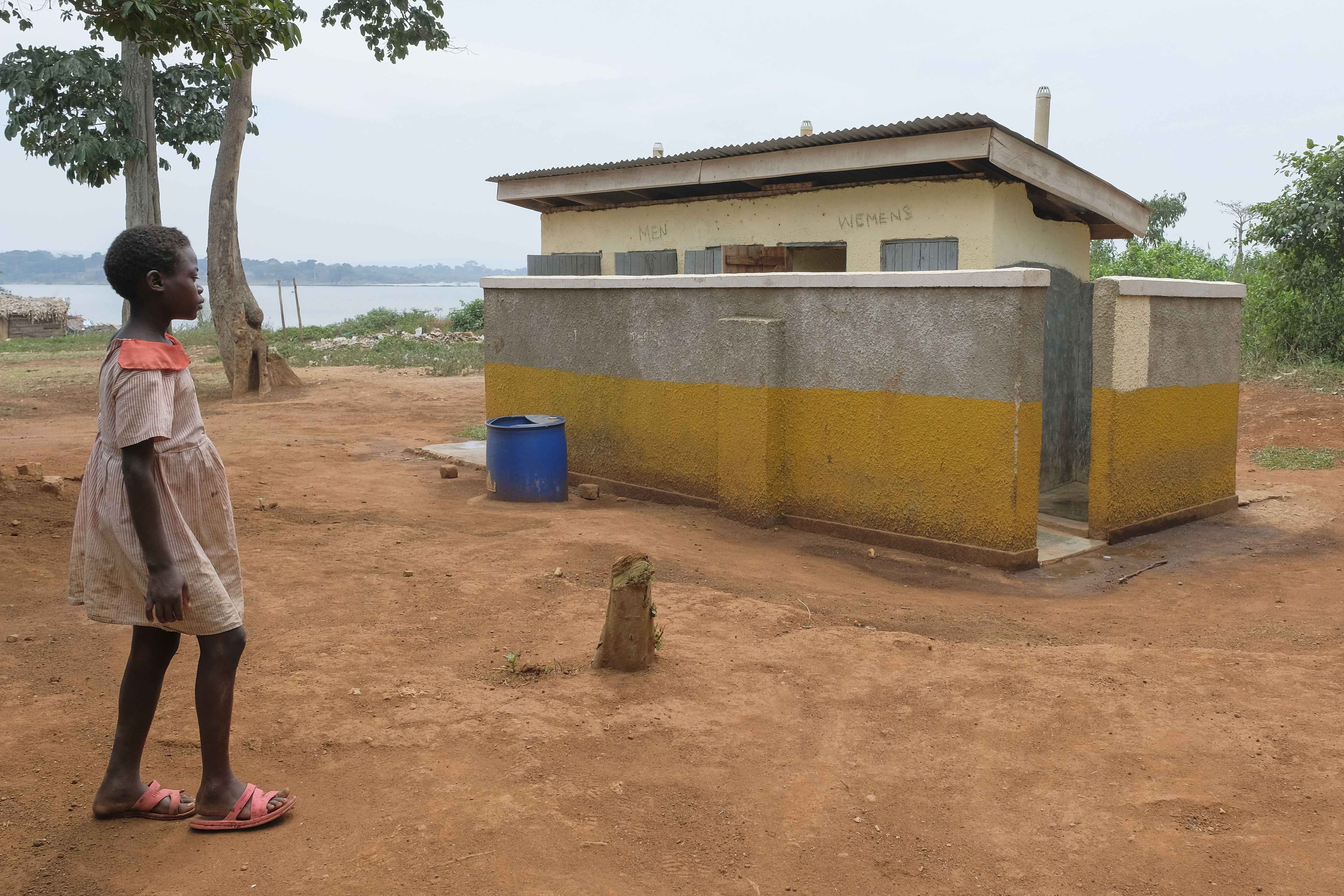 Child standing in front of sanitary facilities and laundry room. In the background Lake Victoria can be seen.
