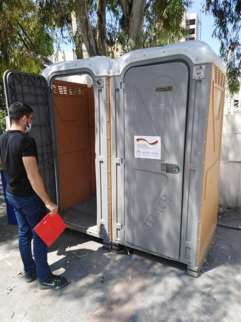 a man looks at a mobile toilet