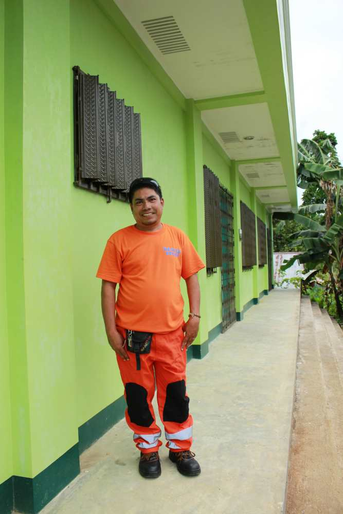 Man with orange clothes in front of green house