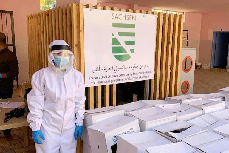 Person in protective suit, mask and gloves next to a stack of cardboard boxes