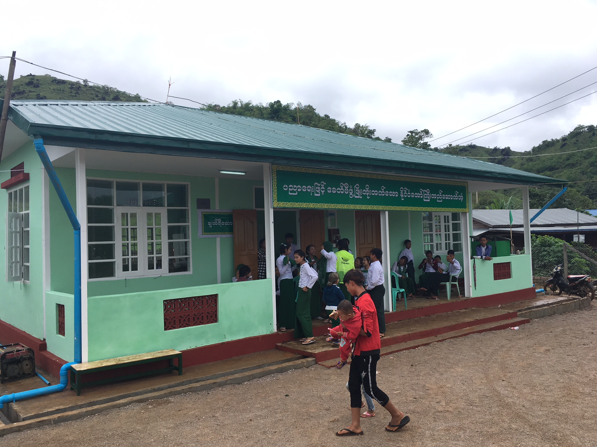 Pupils standing infront of the school building