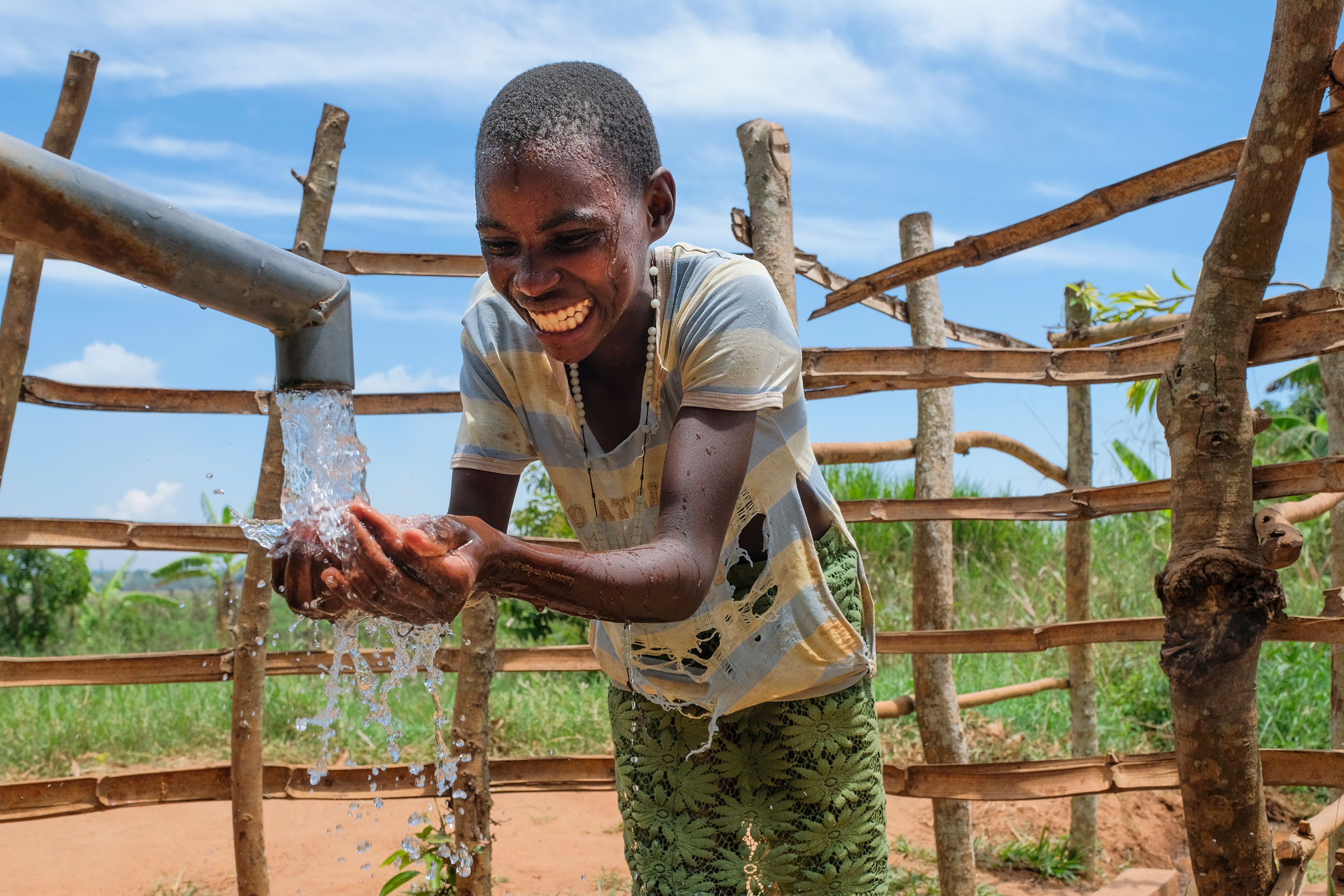 Boy refreshes himself at a well. ©arche noVa