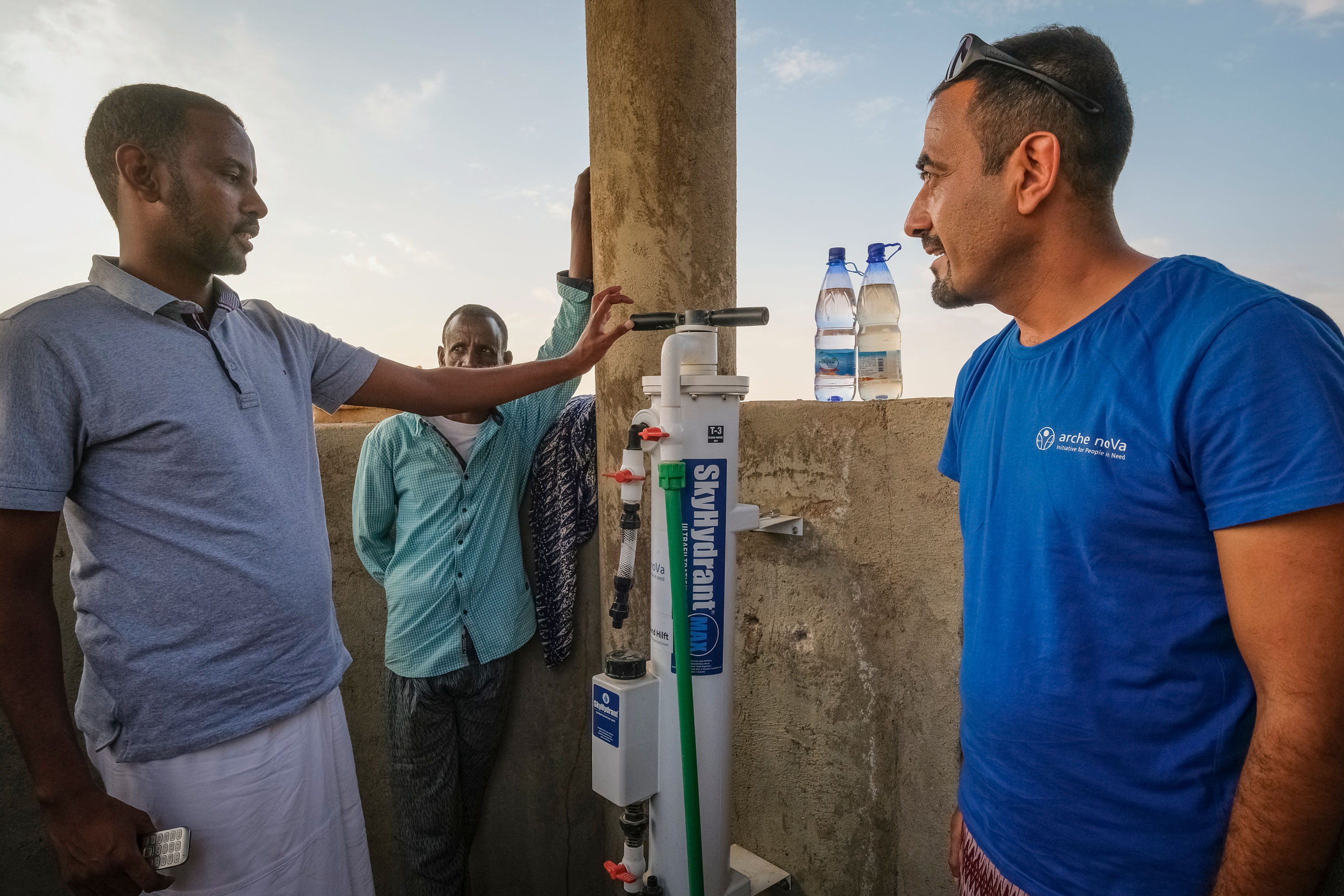 Three men at a drinking water filter