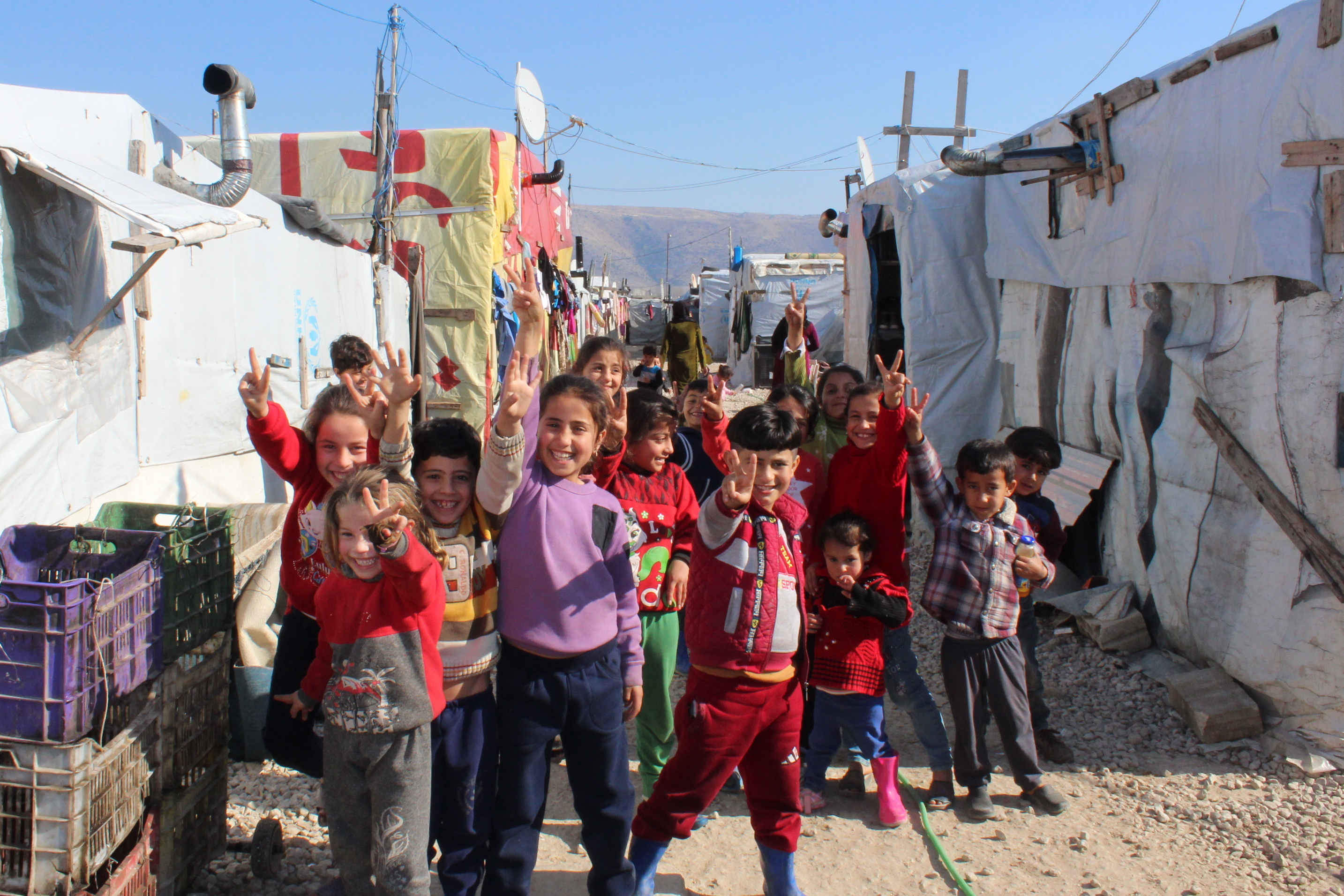 a group of children smiling, in the background are tents of a refugee camp