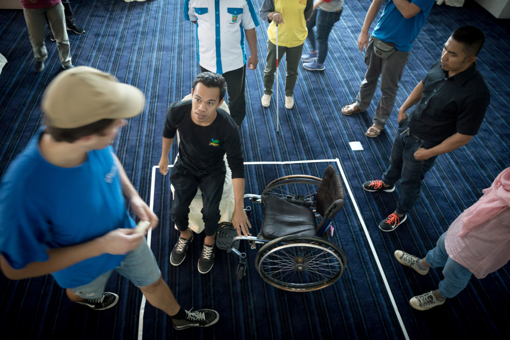 Man standing in front of wheelchair, other people watching