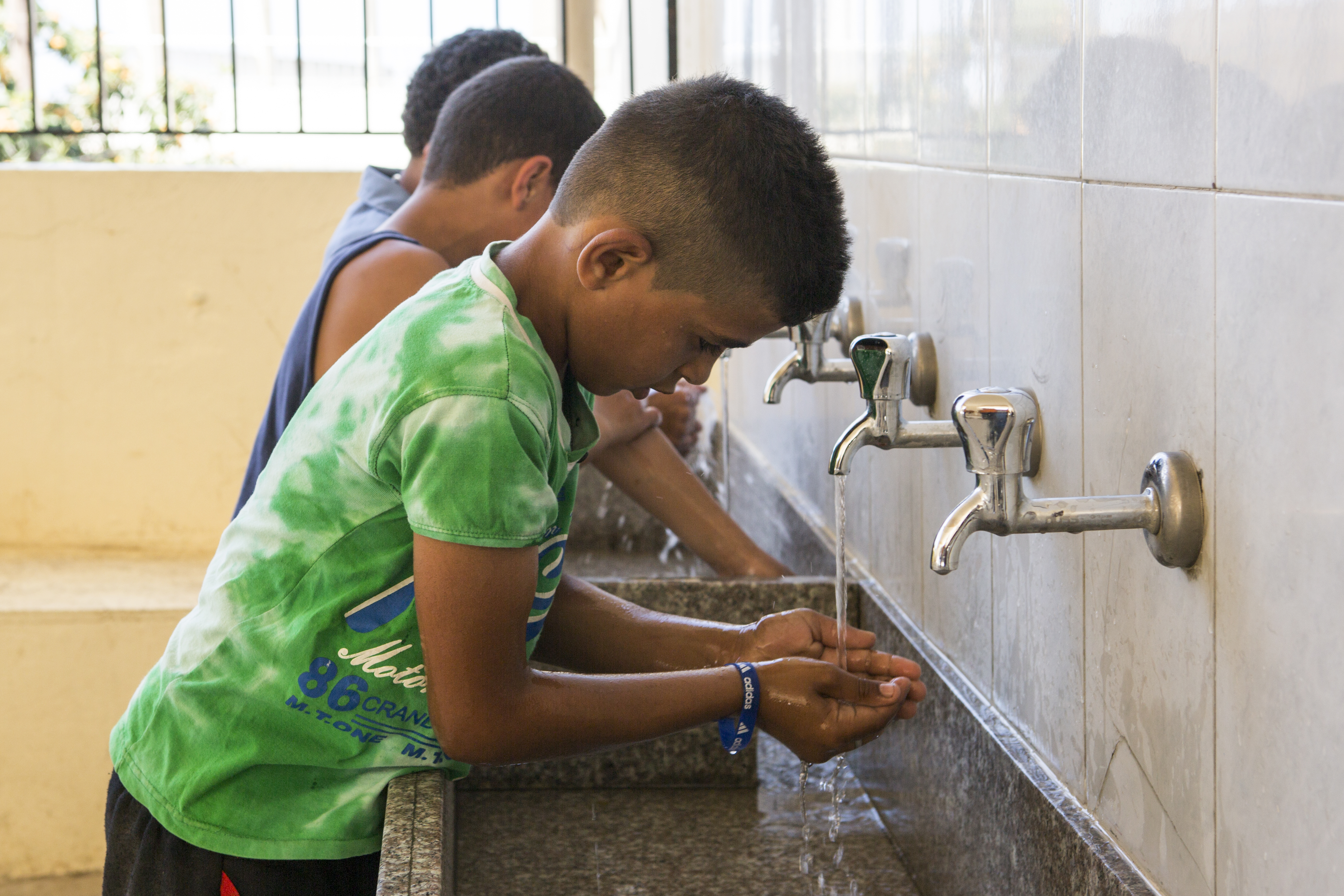 Boy washes his hands.