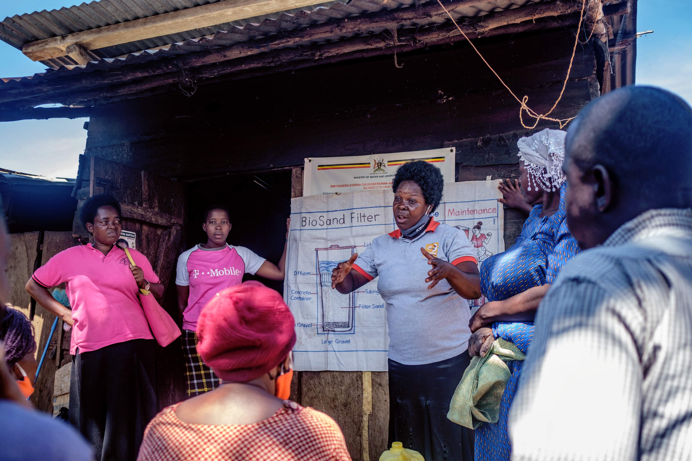 A woman explains the function of bio sand filters to a group of people with diagrams