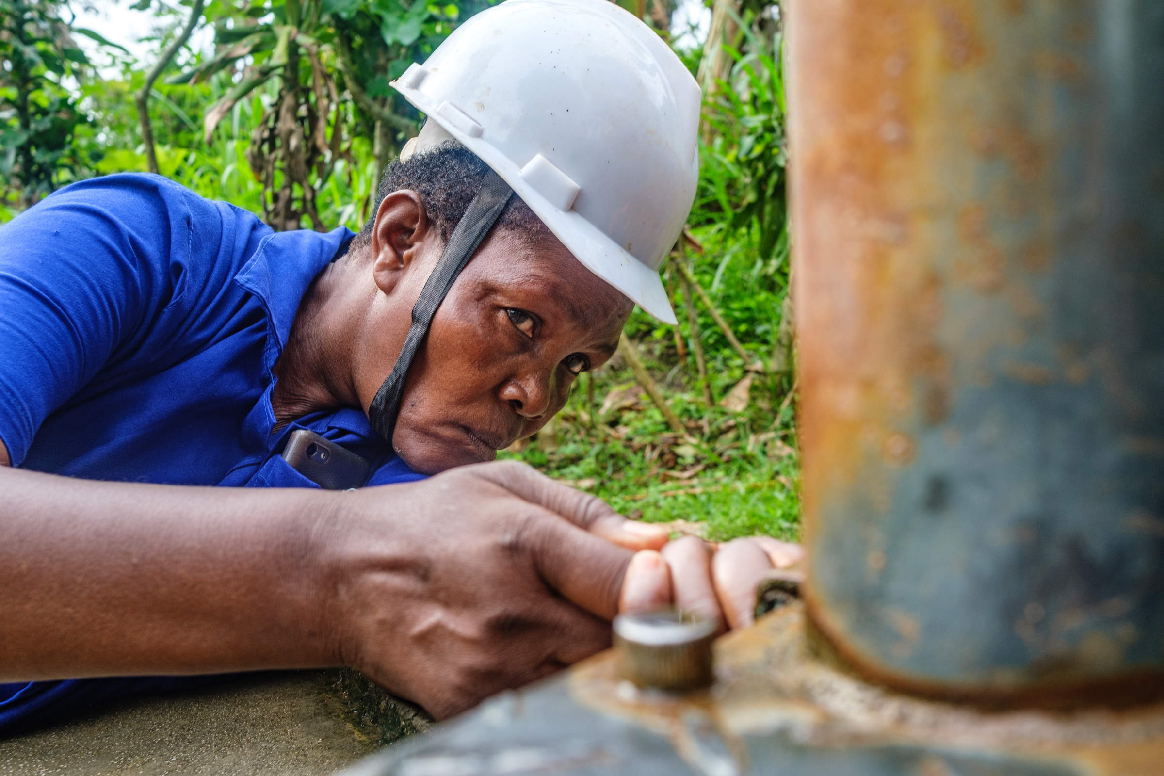 A woman in a safety helmet is concentrating on a well pump.