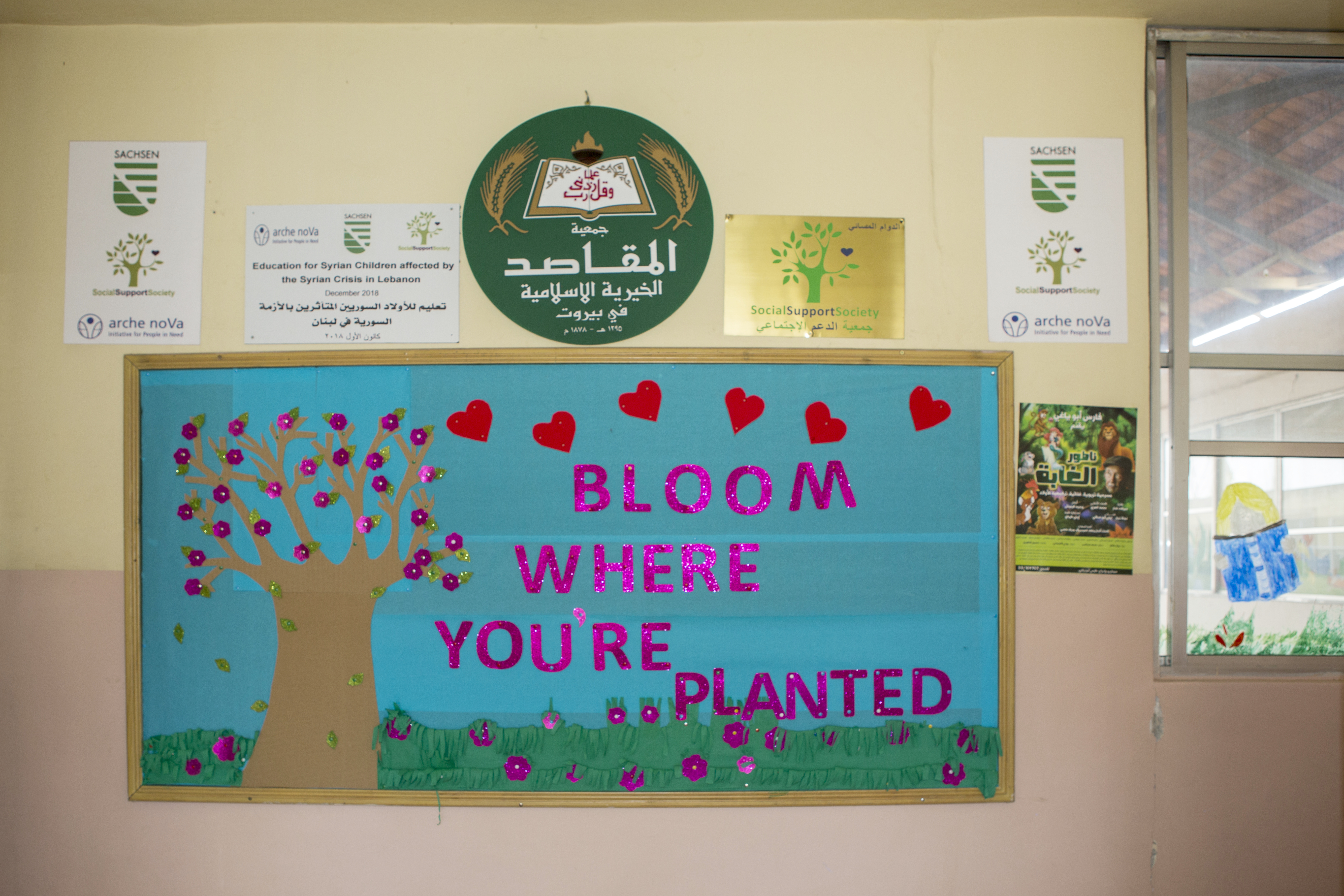 a poster with a greeting and logos of the project partners on a school wall