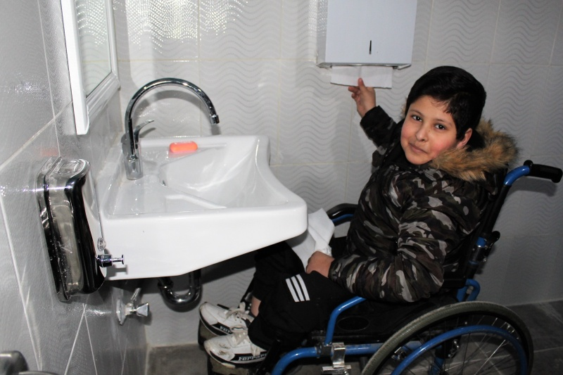 Boy in a wheelchair at a barrier-free hand wash basin