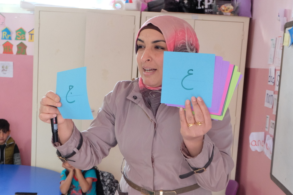 Teacher with cards in hand that have letters written on them
