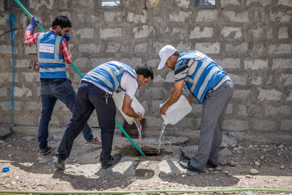 arche noVa staff emptying septic tank in Al-Wand Camp