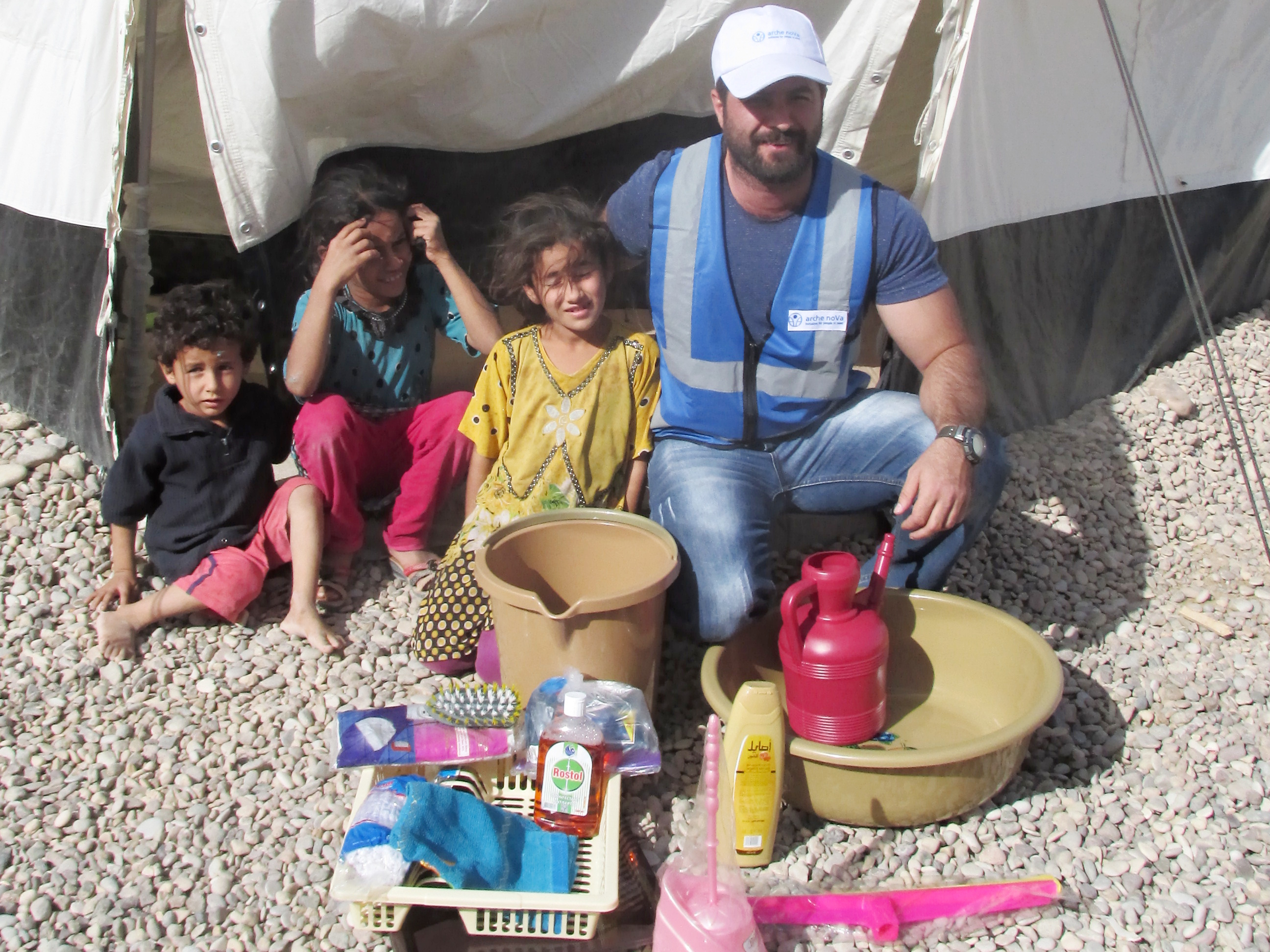 arche noVa member with hygiene kit for a family in front of a tent.