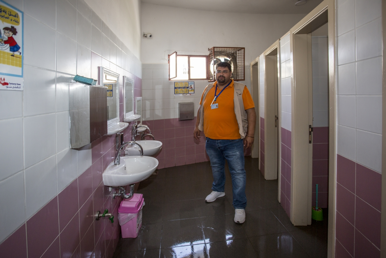 Man in the room with sinks and doors to toilets.