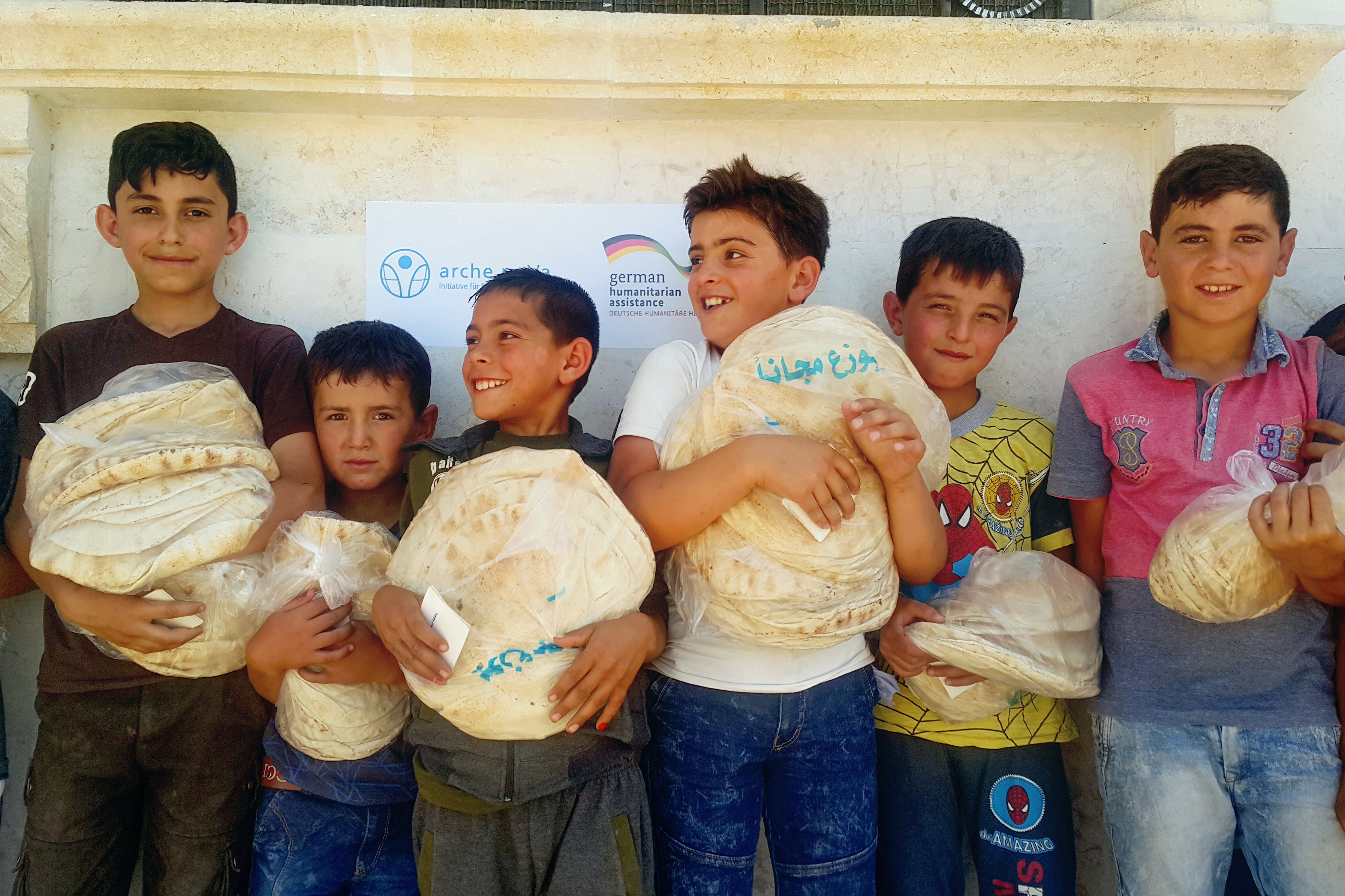 Boys stand in line. They hold packages of bread in front of their chest.