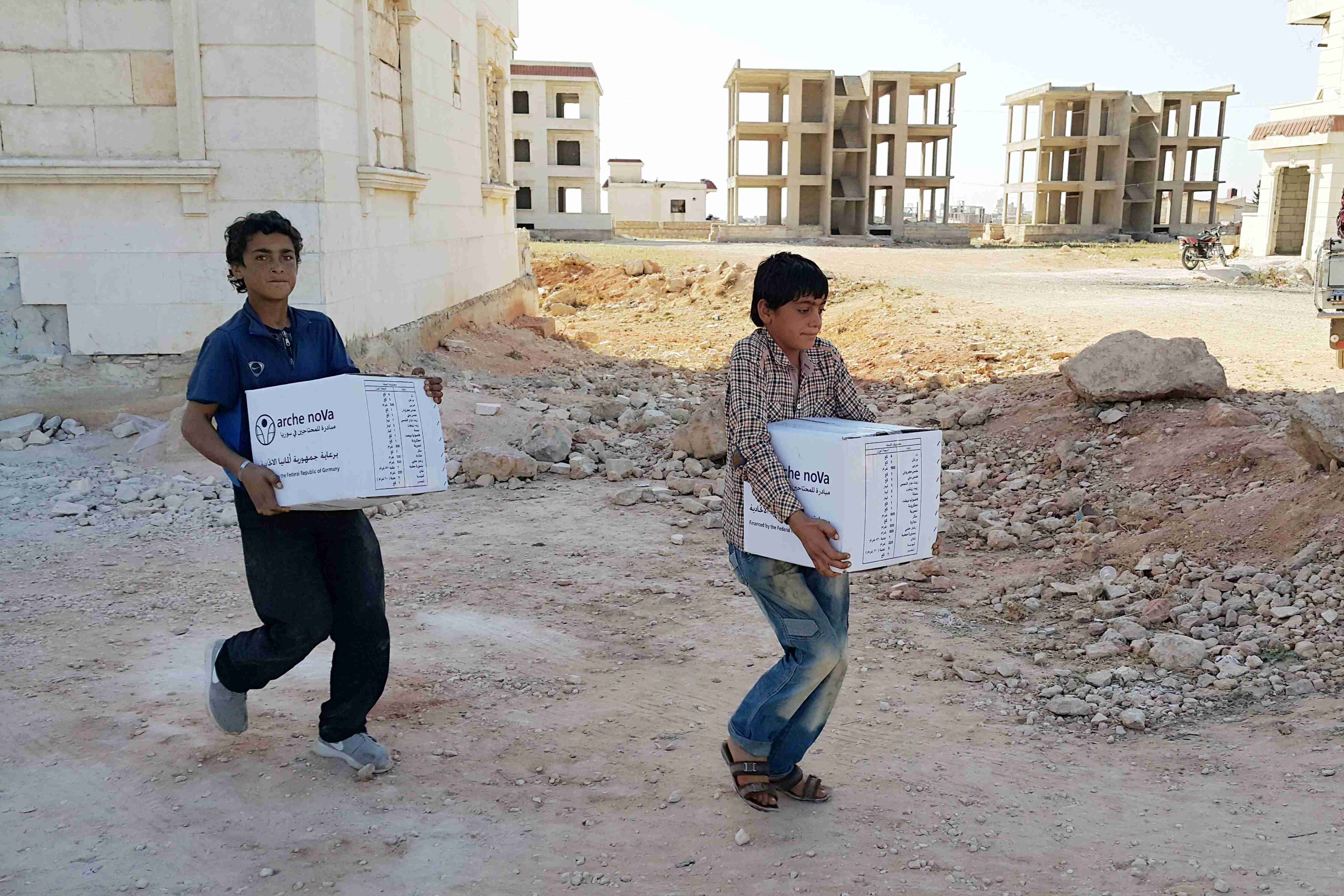 Two boys carrying parcels in front of unfinished buildings