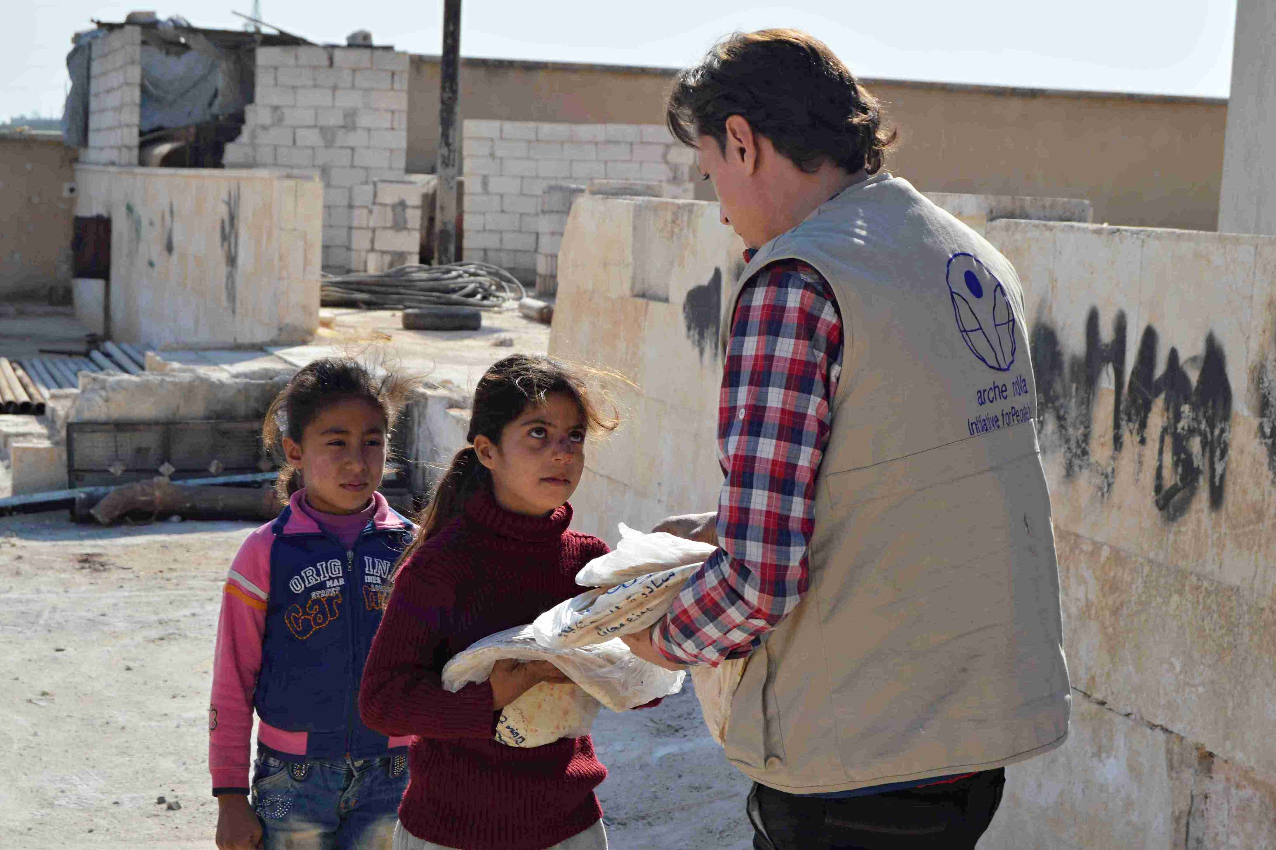 A member of our Syrian team gives bread to a young girl in front of an unfinished building