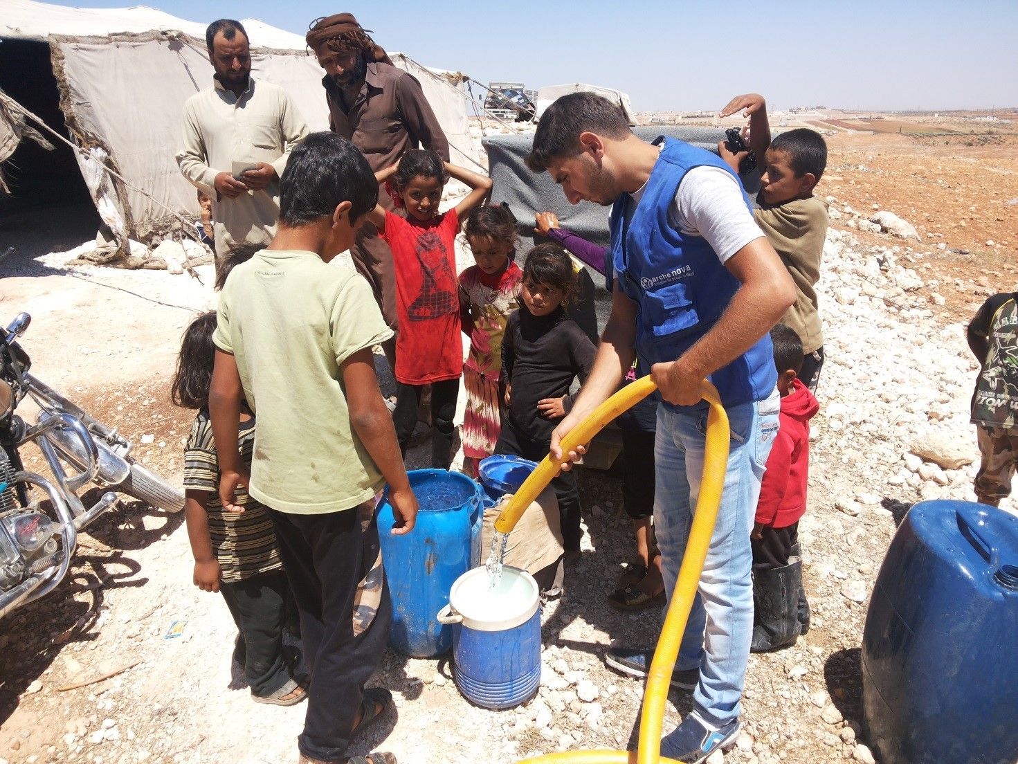 An employee of arche noVa fills buckets and containers with water, children are waiting and watching, there are tents in the background