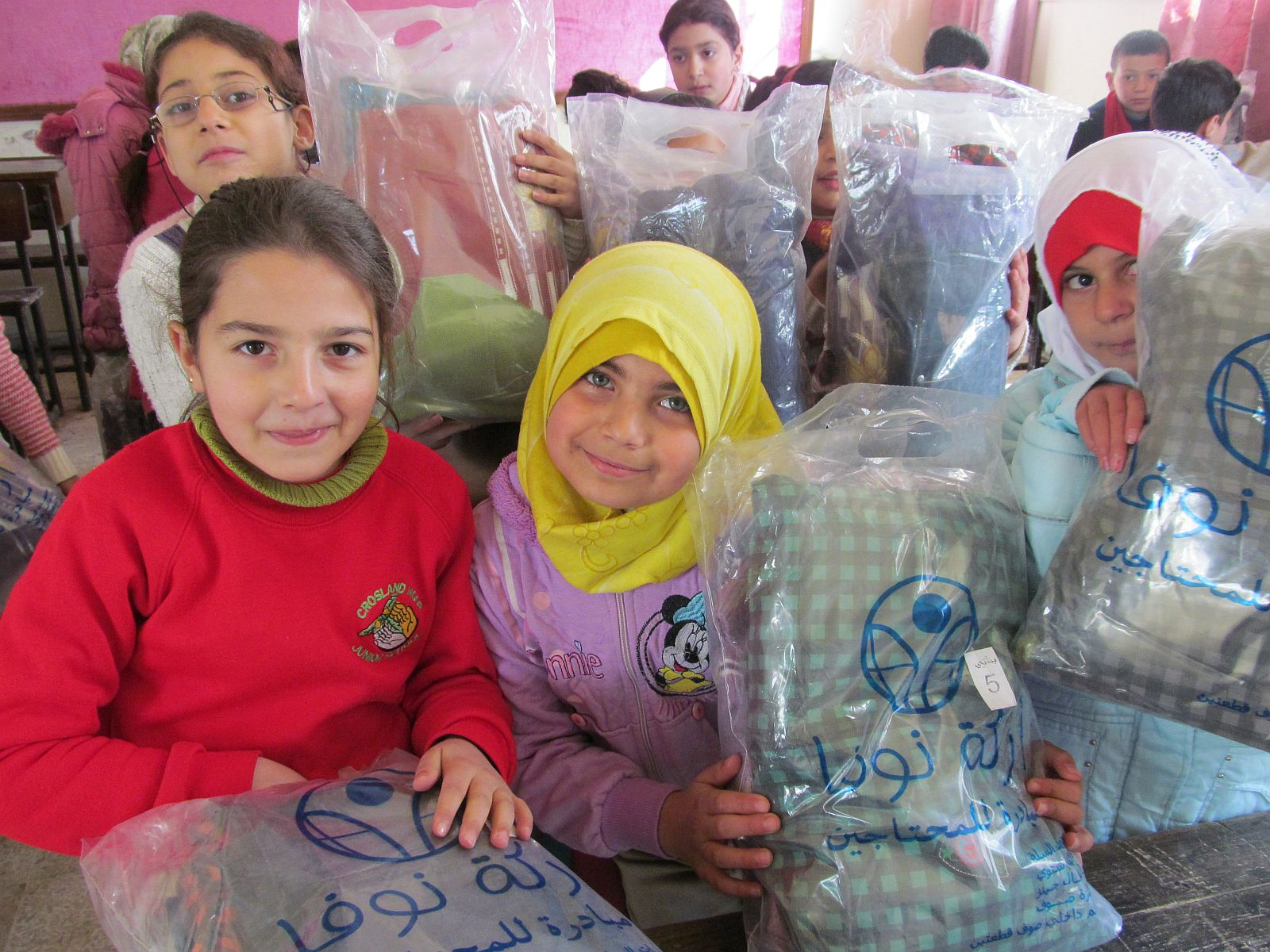 In the classroom: two girls with their classmates holding bags with clothes from arche noVa