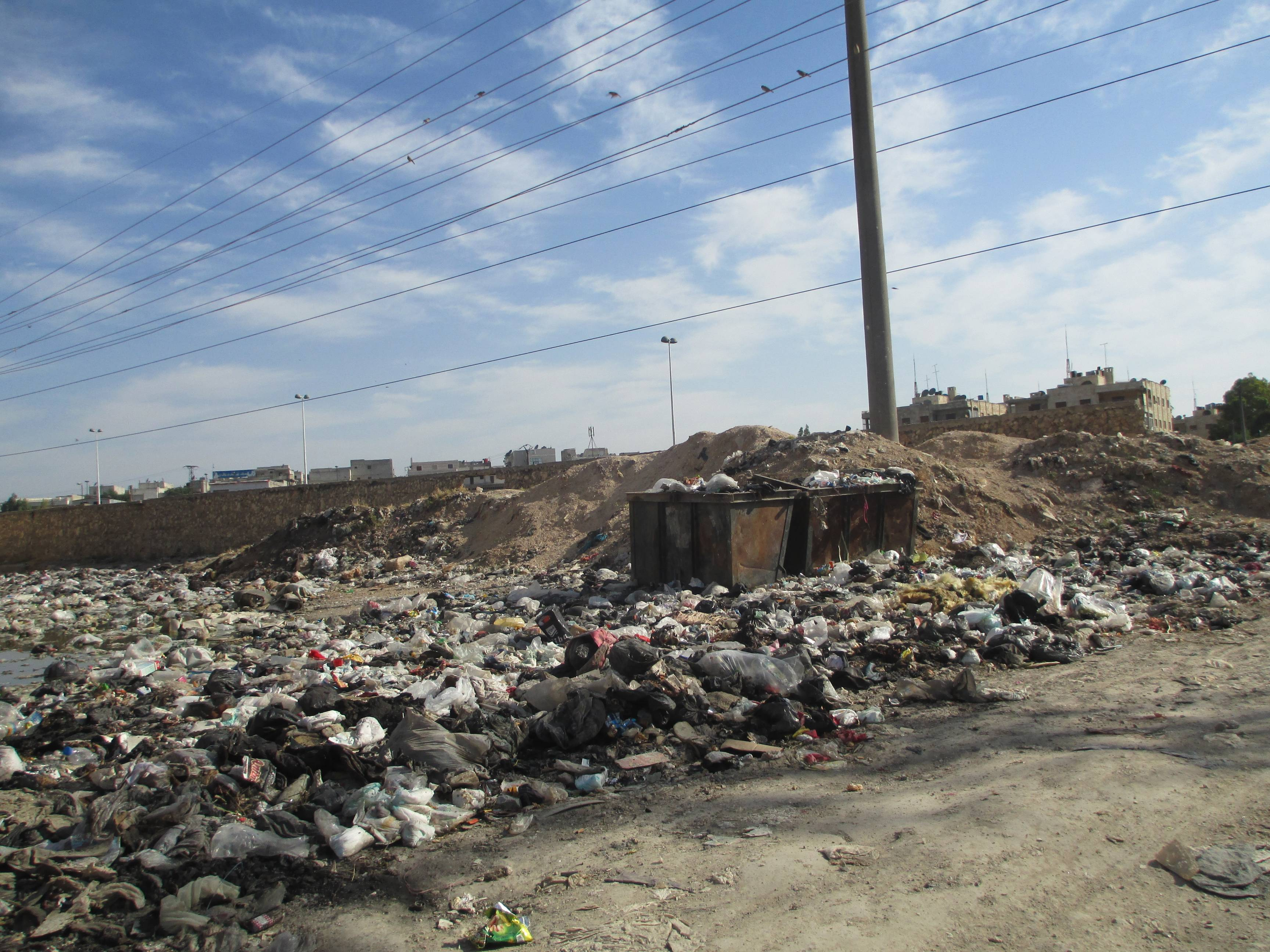 At the gates of a settlement: garbage, bags and refuse piles up in the background