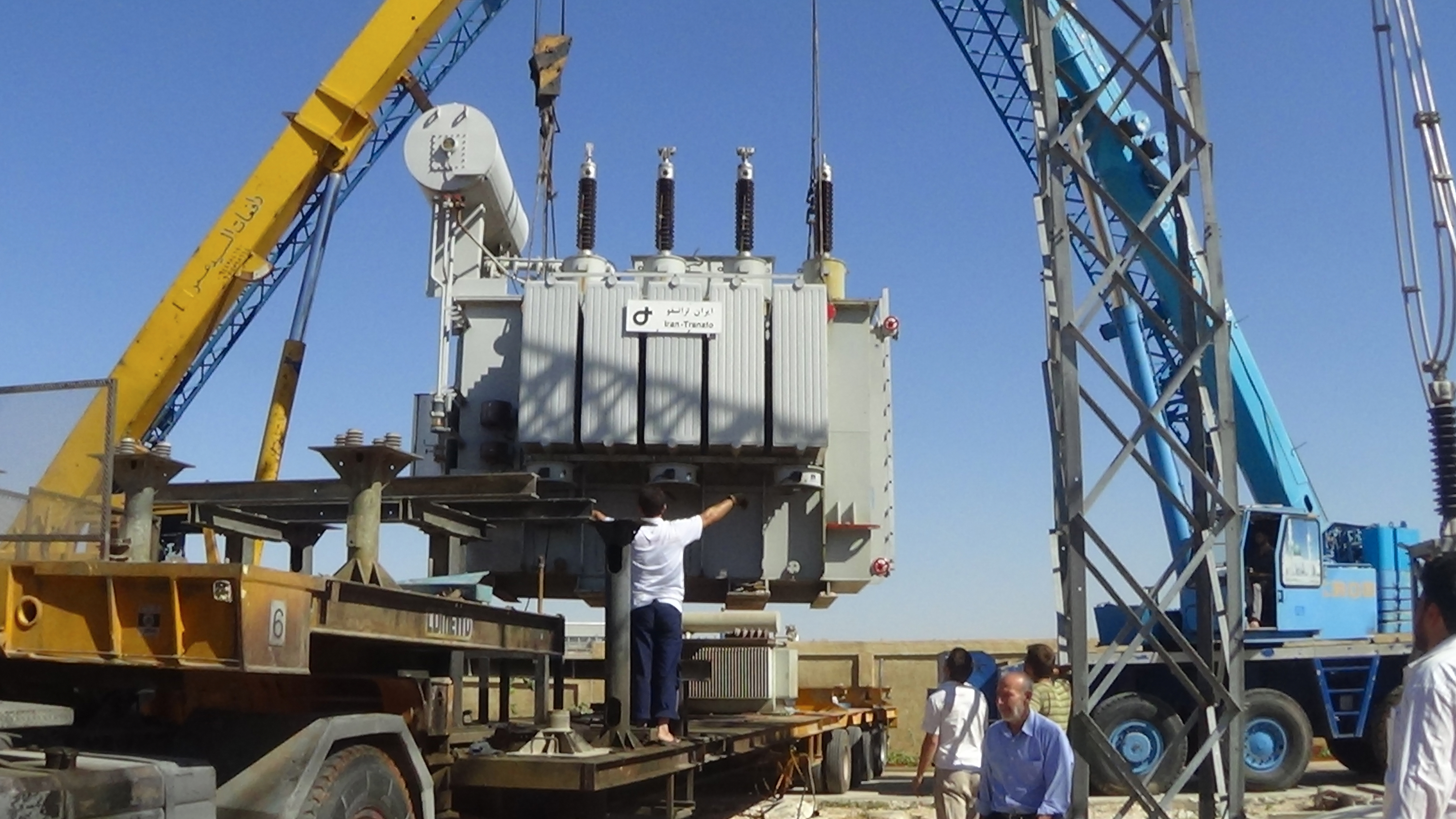A generator the size of a pick-up truck hangs from a crane, technicians conduct the unloading