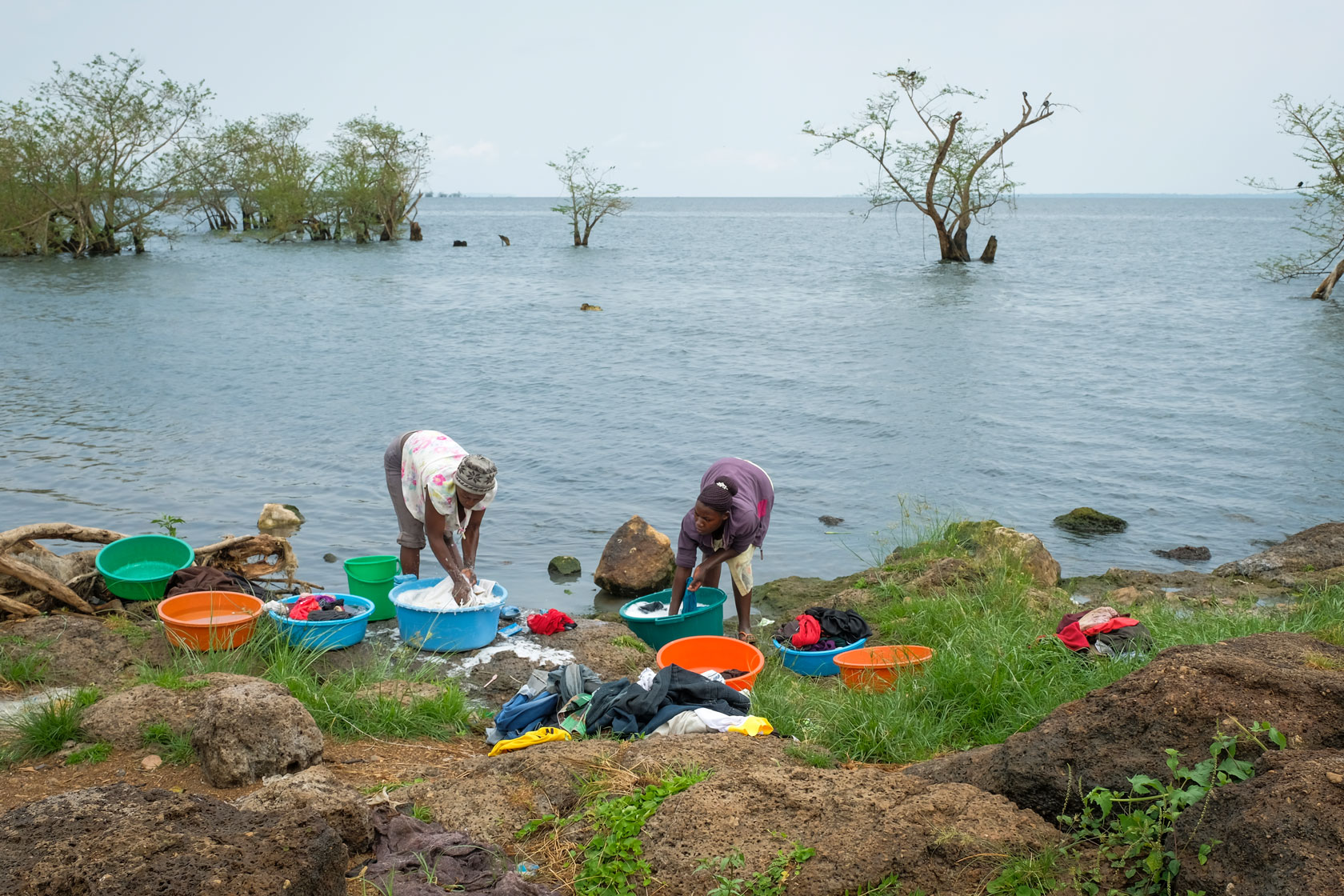 Two women washing laundry with their hands at Lake Victoria