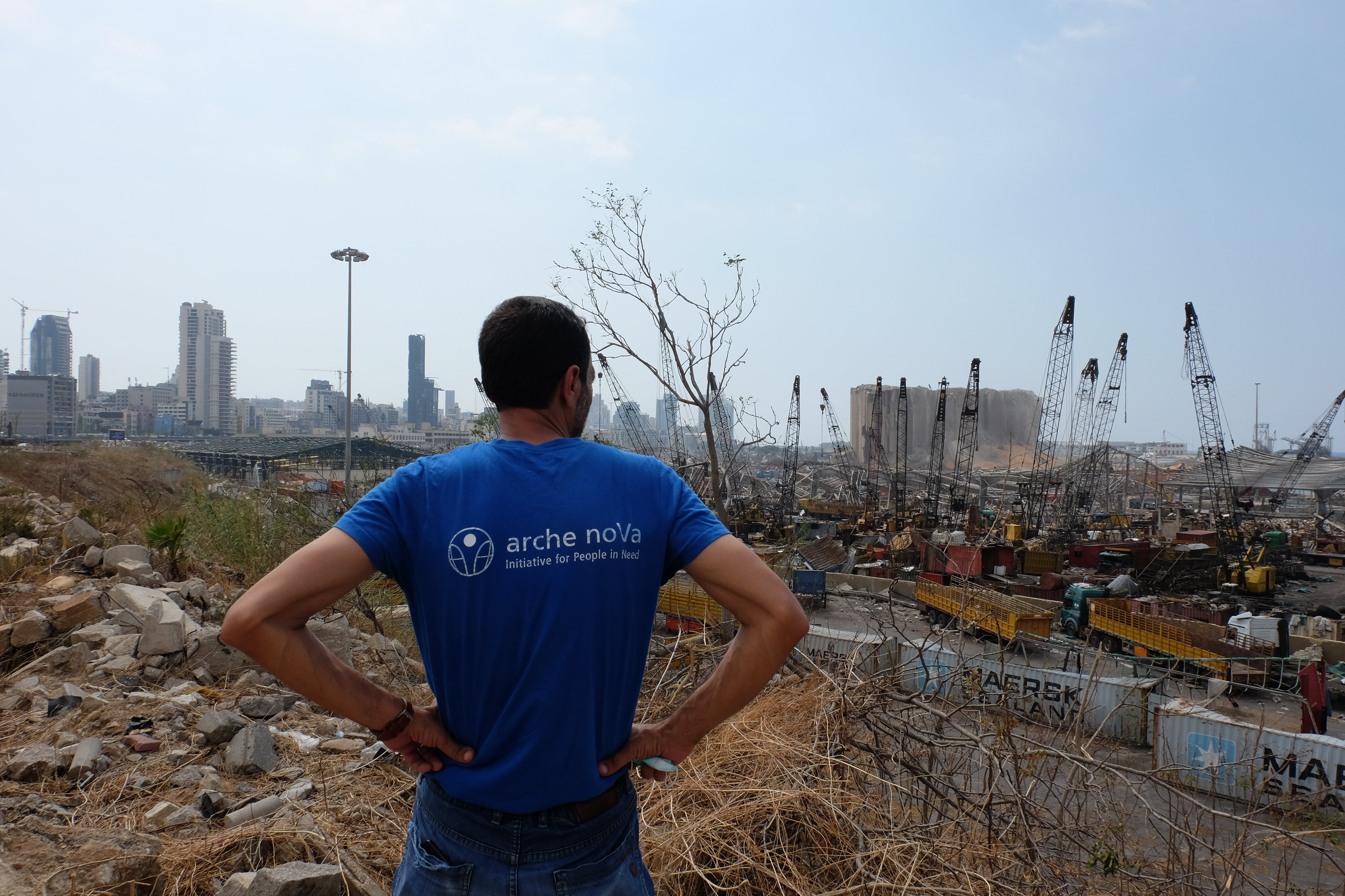 Man looks at destroyed Beirut with folded arms