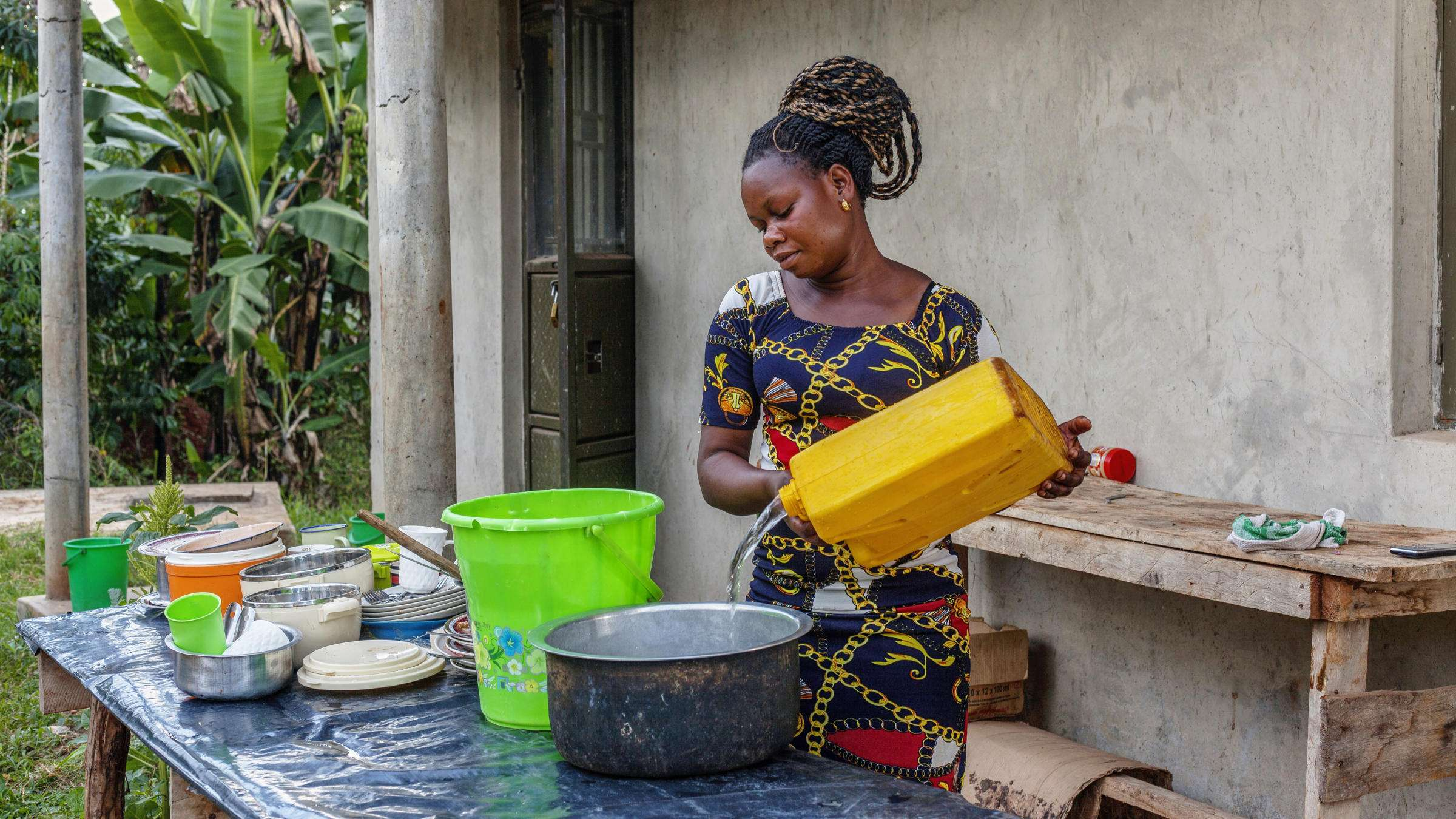 Woman pouring water into wash bowl