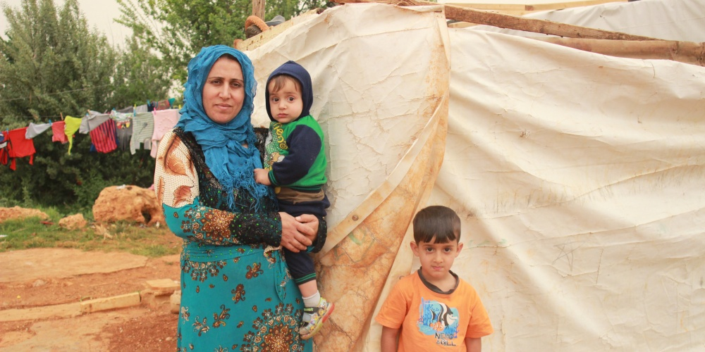 FA woman stands in front of a temporary tent with a small child in her arms, another child next to her.